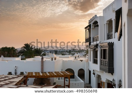 Houses in arabic style with white walls and wooden balconies, background sunset and palm trees
