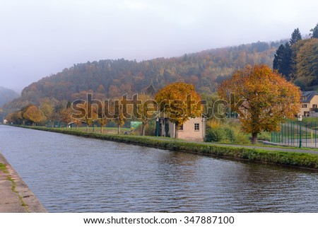 Houses near the river in the autumn forest, France