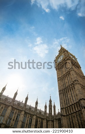 Houses of Parliament and Big Ben in London as seen from below against cloudy sky on a sunny day