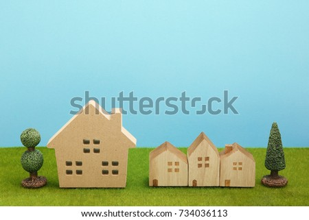 Houses on green grass over blue sky. Mortgage concept.