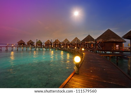 houses on piles on water at night in  fool moon light - stock photo