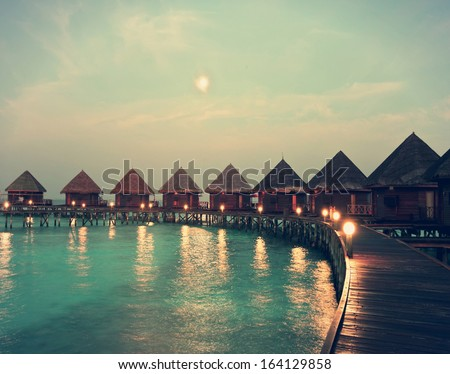 houses on piles on water at night in  fool moon light,with a retro effect - stock photo