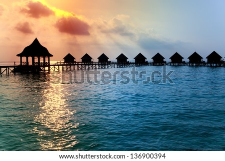 houses on piles on water at the time sunset.