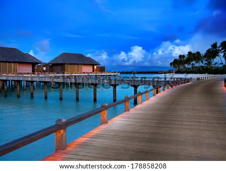 houses on piles on water at the time sunset, Maldives.   - stock photo