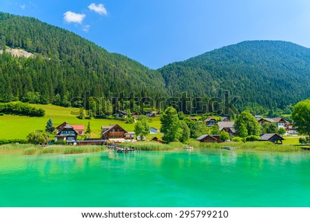 Houses on shore of beautiful Weissensee alpine lake in summer landscape of Alps Mountains, Austria - stock photo