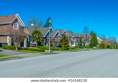 Houses on the empty street. Great and comfortable neighborhood  in the suburbs of Vancouver, Canada. - stock photo