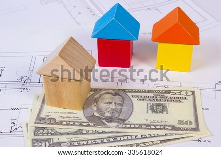 Houses shape made of wooden blocks and currencies dollar lying on electrical construction drawings of house, concept of building house, drawing for projects - stock photo