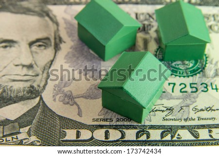 Houses standing on five dollars - stock photo