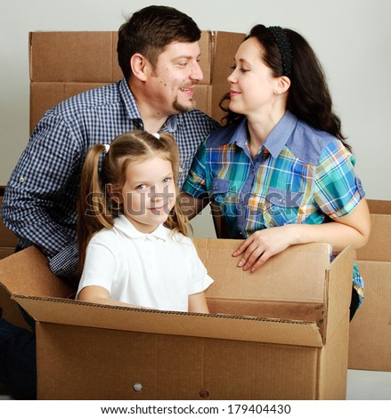 Housewarming. Photo of a young family with a boxes