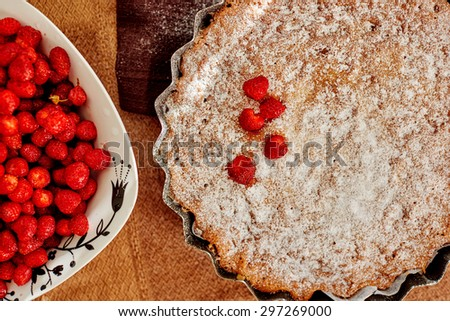 Housewife baked cheesecake with strawberries for their children, sprinkle it with powdered sugar on top and decorated with strawberries - stock photo