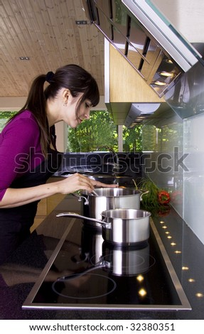 Housewife checking the sauce in a modern kitchen