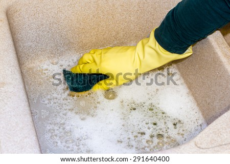 housewife clean the kitchen granite sink with a sponge - stock photo