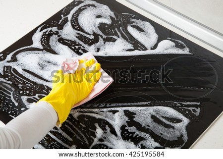 Housewife cleaning an induction plate, closeup shot