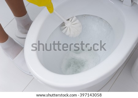 Housewife cleaning out the bowl of the toilet scrubbing under the rim with an antibacterial detergent and brush, close up of her hand