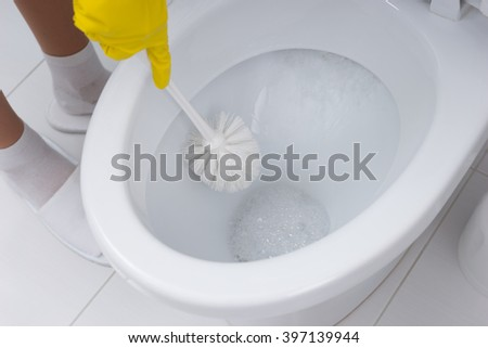 Housewife cleaning the toilet in the bathroom using a toilet brush and antibacterial detergent, close up view of the toilet bowl