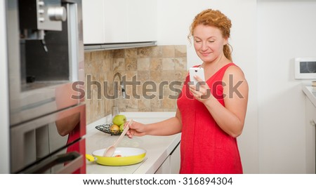 Housewife cooking meal for lunch and looking into mobile phone. Happy lady in red dress smiling in the modern kitchen.