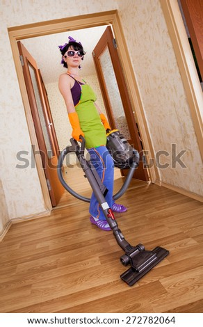 housewife costs in apartment with a vacuum cleaner - stock photo