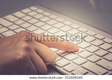 Housewife doing online banking, online shopping, making a payment or purchasing goods on the internet entering her credit card details on a pc, close up view of her hands. - stock photo