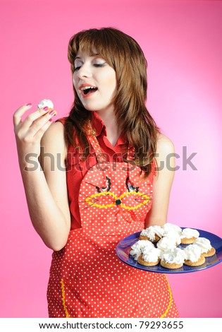 Housewife eats cookies on pink background