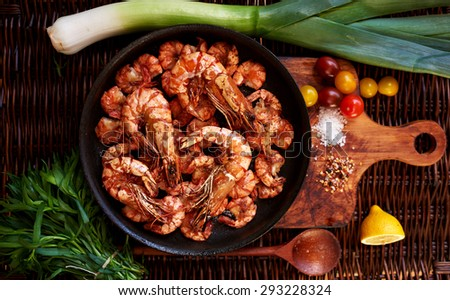 Housewife fries snack for beer, Royal shrimp, tiger prawns, crabs, all laid out on a bright contrast dish served with lemon wedges, cherry tomatoes and parey for fresh spring salad - stock photo