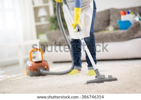 Housewife from cleaning service cleans carpet with vacuum cleaner - stock photo