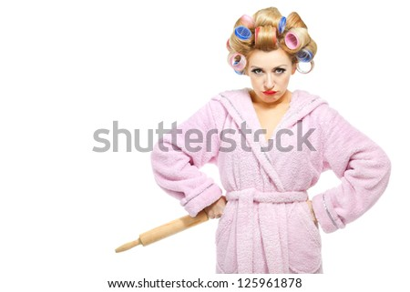Housewife in pink bathrobe with rolling pin on white background - stock photo