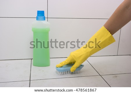 Housewife in rubber gloves clean floor with brush. Cleaning floor in the bathroom.