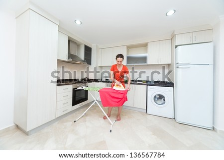 Housewife ironing laundry in the middle of the kitchen - stock photo