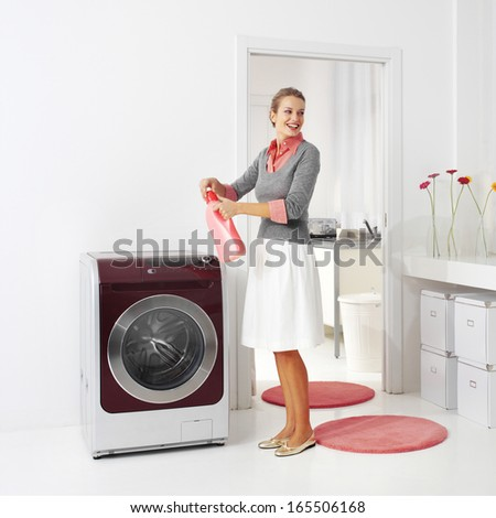 housewife keeps detergent near the washing machine in laundry room - stock photo