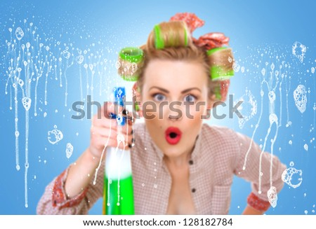 Housewife  or woman behind window spraying the cleaner on glass. Focus on soap - stock photo