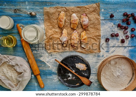 Housewife prepared for dessert bagels stuffed with cherries and jam, sprinkle with powdered sugar - stock photo