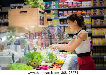 Housewife shopping in supermarket. - stock photo