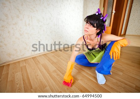 housewife sits on a floor and cleans a floor - stock photo