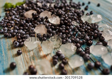 Housewife sprinkled fresh berries with ice to freeze them - stock photo