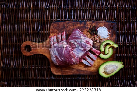 Housewife washed lamb chops and marinate them gathered for lunch on a brown wicker table is a board on which the fresh meat of lamb, sliced avocado is near - stock photo