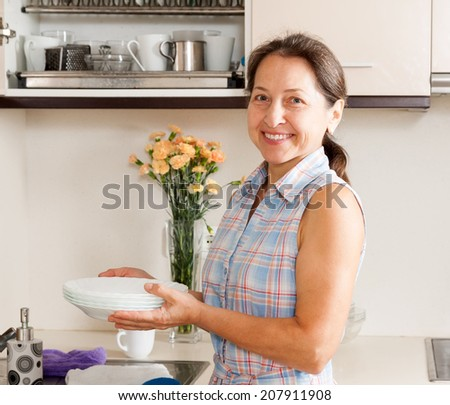 housewife washing plates  in domestic kitchen