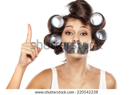 Housewife with curlers and adhesive tape over her mouth he wants to tell you something - stock photo