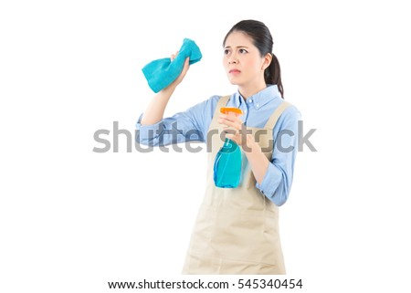 Housewife with disgusted expression cleaning dirty glass doing the housework while using a spray. isolated on white background. mixed race asian chinese model.