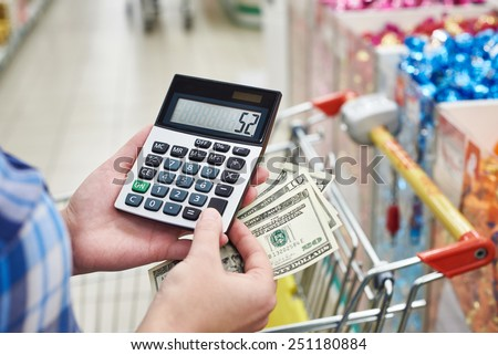 Housewife with dollars and calculator considers costs in the store - stock photo
