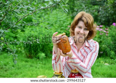 Housewife with homemade pickles and jams in the garden