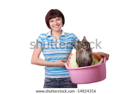 Housewife with laundry basket with dirty cat.  A young woman holding a basket of folded laundry. Time for laundry day. - stock photo