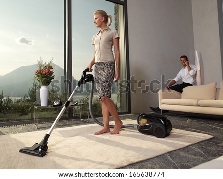 housewife with vacuum cleaner in a room - stock photo