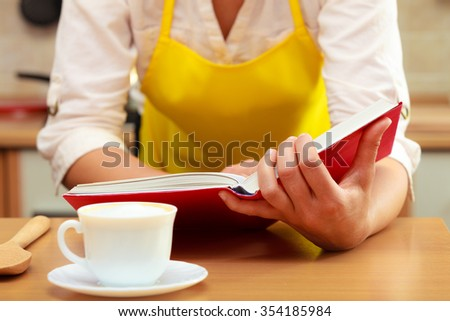 Housewife woman reading cookbook in kitchen. Female in apron at home. - stock photo