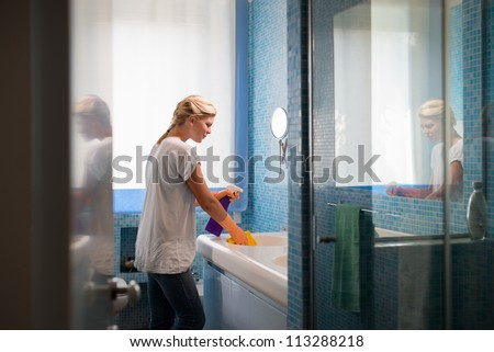 Housework and domestic lifestyle: woman doing chores in bathroom at home, cleaning wash basin and tap with spray detergent - stock photo