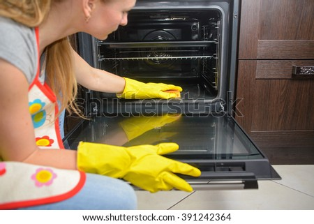 housework and housekeeping concept - close up of woman hand in protective glove with red rag cleaning oven at home kitchen - stock photo