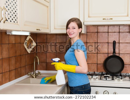 Housework and housekeeping concept. Young woman with cleaning spray bottle happy and smiling cleaning domestic kitchen. Housewife cleaning sink in kitchen with detergent. - stock photo