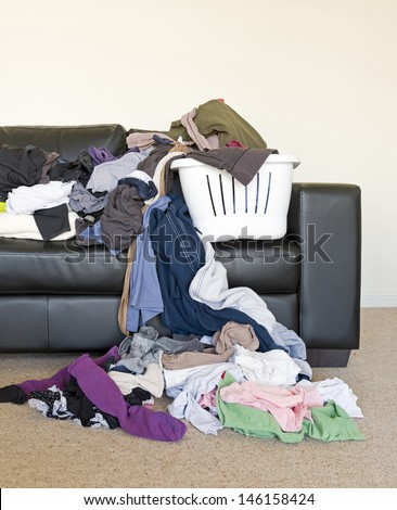 Housework concept of a large pile of laundry dumped on the couch, waiting to be folded and put away - stock photo