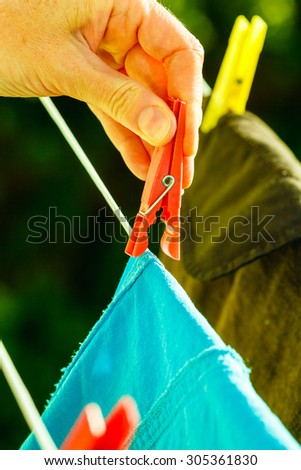 Housework. Woman hand hanging clean wet laundry to dry on the rope clothes line outdoor.