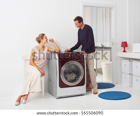 Housework, young woman and man doing laundry at home - stock photo