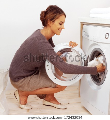 Housework, young woman doing laundry - stock photo